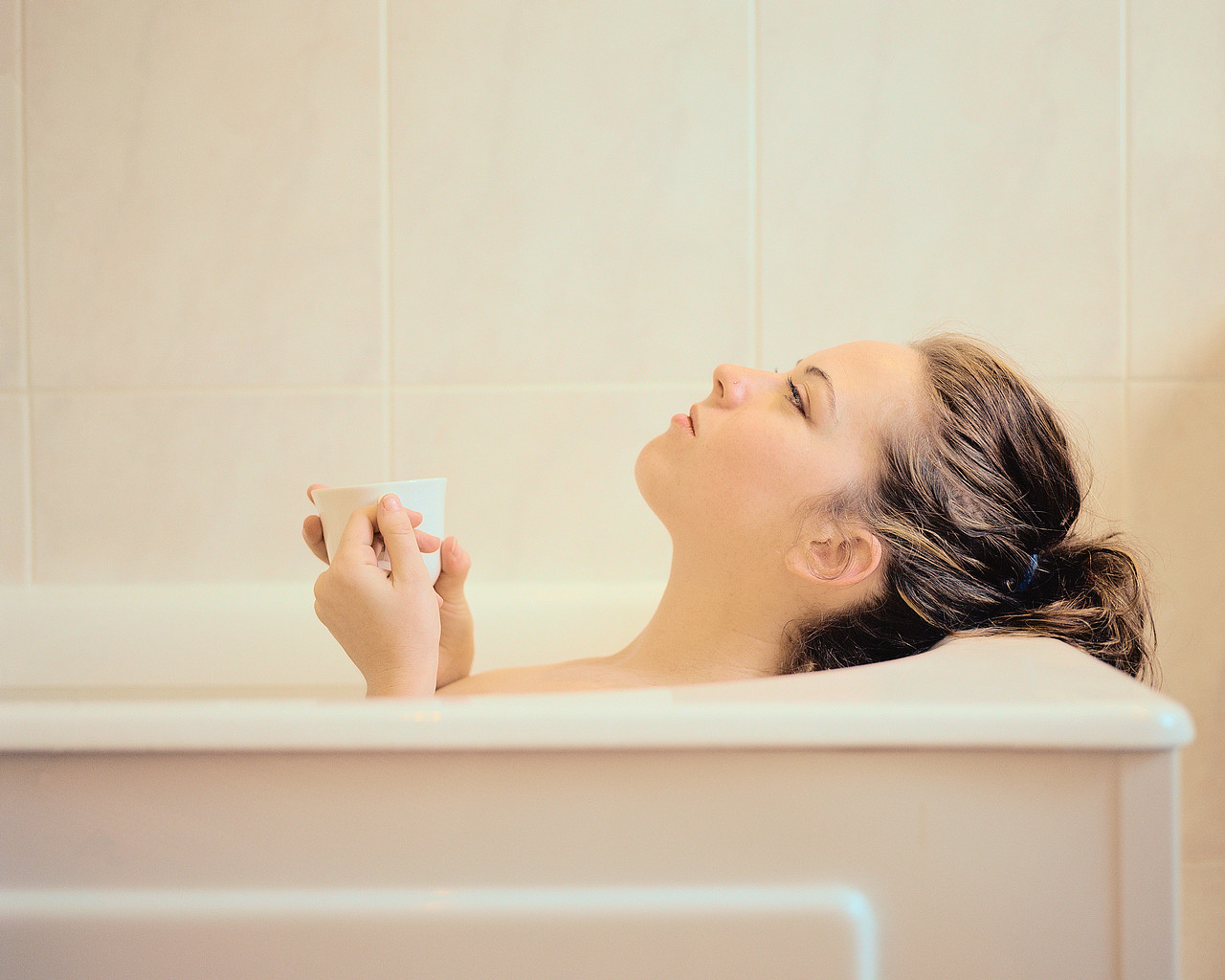 Woman Lying in a Bathtub Holding a Mug ca. 2001